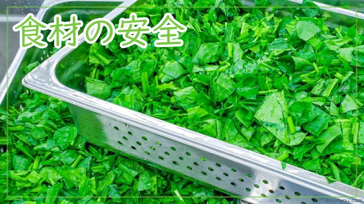 給食の食材の安全。葉物野菜が大量調理用のコンテナざるに入っている写真。